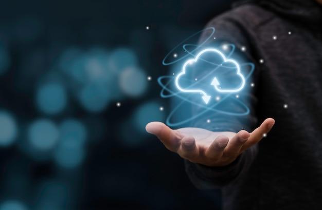 Uomo d'affari che tiene il cloud computing virtuale per trasferire le informazioni sui dati e caricare l'applicazione di download. concetto di trasformazione tecnologica.