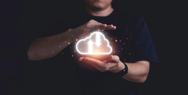 Uomo d'affari in possesso di cloud computing virtuale per trasferire informazioni sui dati e caricare l'applicazione di download. concetto di trasformazione della tecnologia.