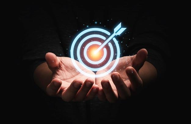 Uomo d'affari che tiene il bersaglio virtuale con la freccia, imposta il concetto dell'obiettivo dell'obiettivo di business achievement.
