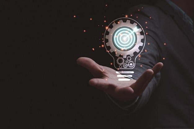 Uomo d'affari che tiene lampadina virtuale che contiene ingranaggio meccanico e scheda obiettivo, idea di pensiero creativo per il concetto di successo aziendale.