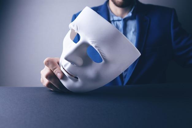Uomo d'affari che tiene maschera bianca in mano