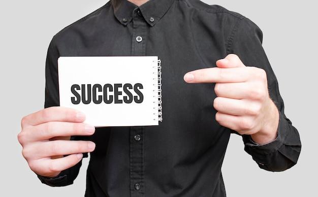 Uomo d'affari che tiene un blocco note bianco con il testo successo, concetto di affari