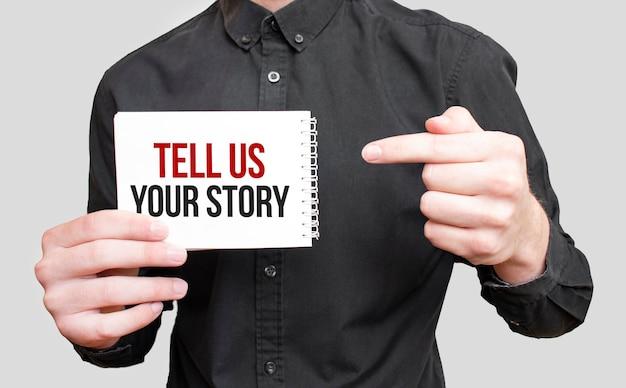 Uomo d'affari che tiene un blocco note bianco con testo raccontaci la tua storia