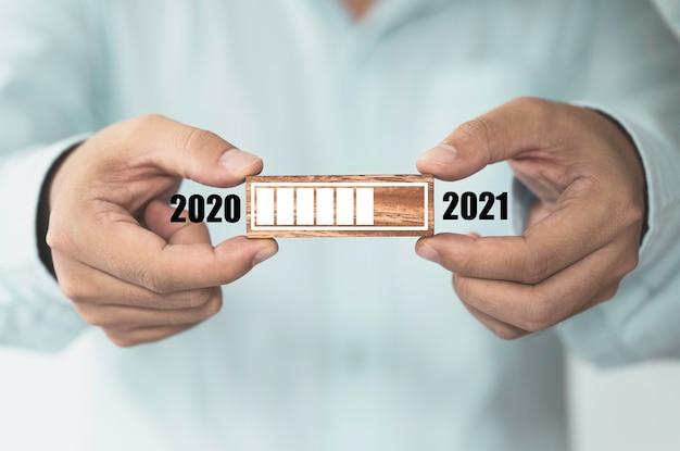 Uomo d'affari che tiene blocco cubo di legno che stampa il caricamento dello schermo per l'anno 2020 all'anno 2021, inizia un nuovo concetto di business.