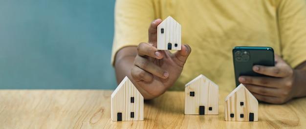 Uomo d'affari che tiene casa in legno per la prenotazione di proprietà immobiliari tramite smartphone tecnologia aziendale assicurativa casa utilizzare per sito web con banner
