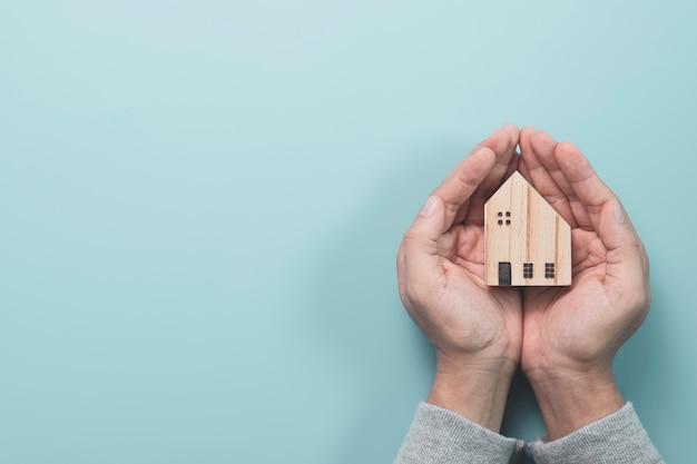 Uomo d'affari che tiene modello di casa in legno su sfondo blu, proteggere la casa e il concetto di asset.
