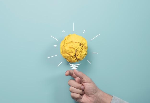 Uomo d'affari che tiene palla gialla della carta di scarto con la pittura dell'illustrazione per la lampadina virtuale. è un'idea di pensiero creativo e un concetto di innovazione.