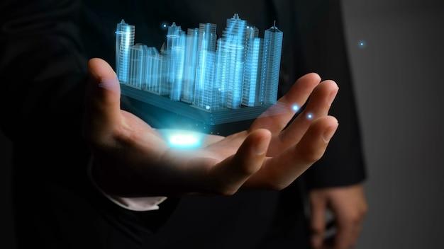 L'uomo d'affari tiene il modello 3d della città che mostra la tecnologia della realtà aumentata