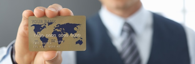 L'uomo d'affari tiene un primo piano della carta di credito