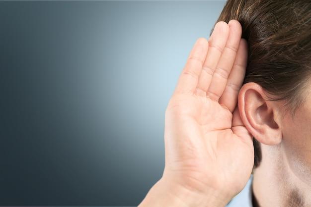 L'uomo d'affari tiene la mano vicino all'orecchio e ascolta qualcosa