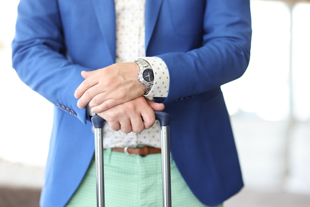 L'uomo d'affari tiene le sue mani sul manico della valigia