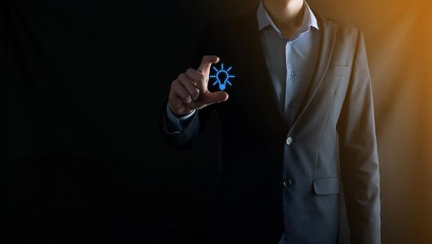 L'uomo d'affari tiene la lampadina dell'icona di idea su priorità bassa di tono scuro