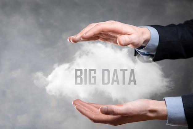 L'uomo d'affari tiene la scritta big data in una nuvola.