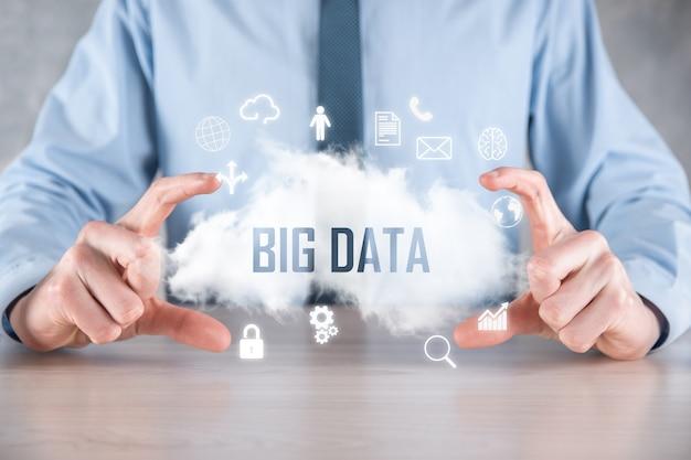 L'uomo d'affari tiene l'iscrizione big data. lucchetto, cervello, uomo, pianeta, grafico, lente di ingrandimento, ingranaggi, nuvola, griglia, documento, lettera, icona del telefono.
