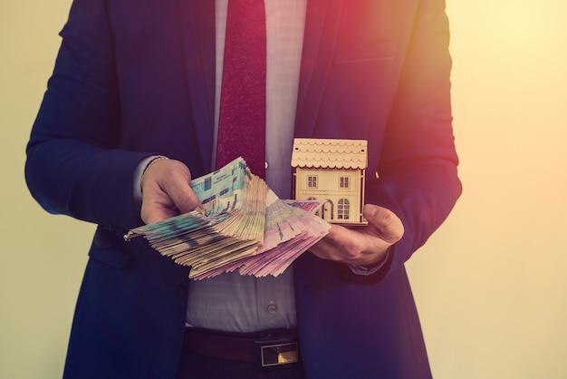 L'uomo d'affari tiene le chiavi dell'appartamento con i soldi di qualcuno dopo aver venduto o affittato una casa. stipulare un accordo di successo