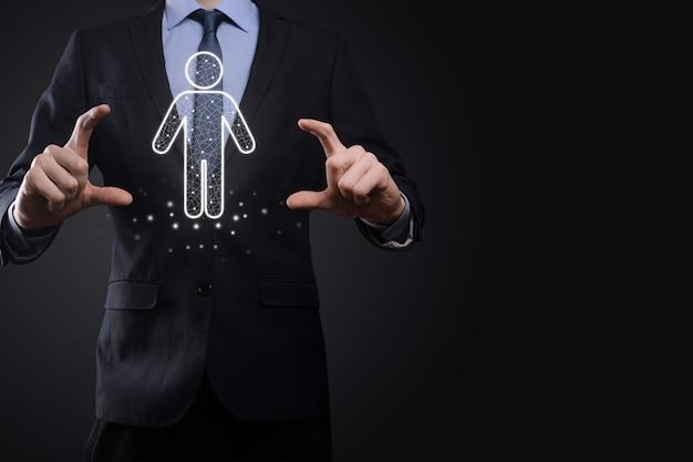 L'uomo d'affari tiene l'icona della persona dell'uomo sullo sfondo di tono scuro. hr human, people icontechnology process system business con reclutamento, assunzione, team building. concetto di struttura organizzativa.
