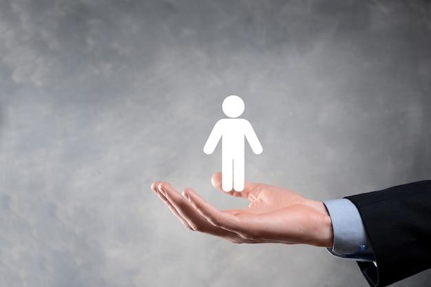 L'uomo d'affari tiene l'icona della persona dell'uomo sulla parete di tono scuro.