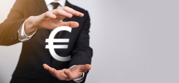 L'uomo d'affari tiene le icone delle monete in euro o in euro su sfondo scuro.. crescente concetto di denaro per investimenti aziendali e finanza