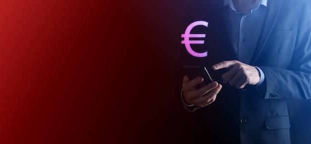 L'uomo d'affari tiene le icone della moneta dei soldi eur o euro su fondo di tono scuro. concetto di denaro in crescita per investimenti aziendali e finanza.