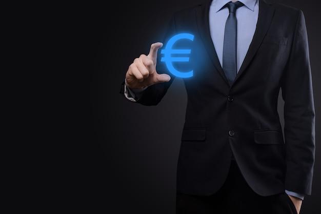 L'uomo d'affari tiene le icone della moneta dei soldi eur o euro sulla superficie di tono scuro