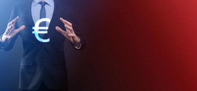 L'uomo d'affari tiene i simboli della moneta dei soldi eur o euro su fondo di tono scuro. concetto di denaro in crescita per investimenti e finanza aziendale.