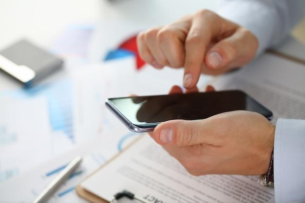Un uomo d'affari tiene un nuovo smartphone