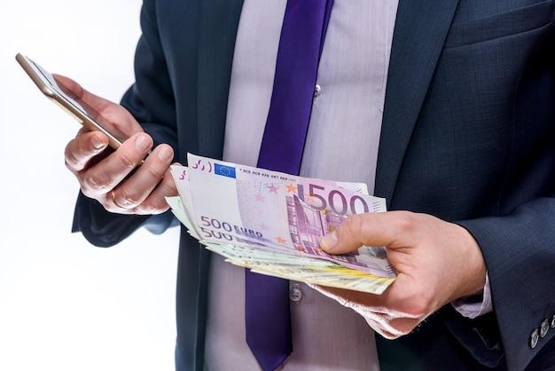 L'uomo d'affari tiene in una mano l'euro e un altro telefono