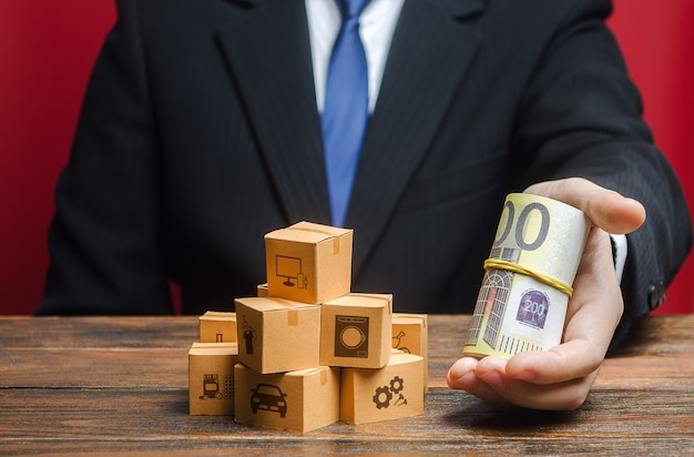 Un uomo d'affari porge un pacco di euro vicino a una pila di scatole.