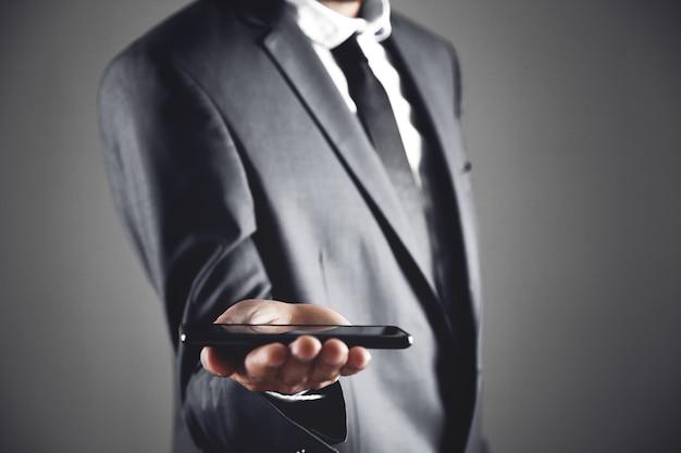 L'uomo d'affari tiene il telefono in mano