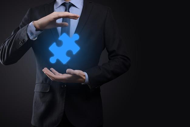 Uomo d'affari tiene un pezzo di puzzle nelle sue mani il concetto di cooperazione, lavoro di squadra, aiuto e supporto negli affari.