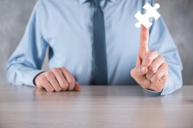 Imprenditore tiene un pezzo di puzzle nelle sue mani. il concetto di cooperazione, lavoro di squadra, aiuto e supporto negli affari.
