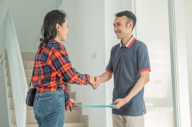 Imprenditore sviluppatore di alloggi consegna certificato di casa alla bella donna mentre si stringono la mano in casa