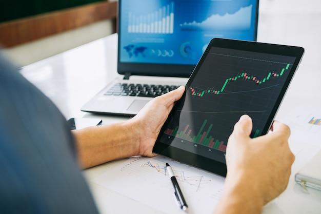 L'uomo d'affari investe il prezzo del bitcoin sul mercato dello scambio di grafici digitali concetto di criptovaluta