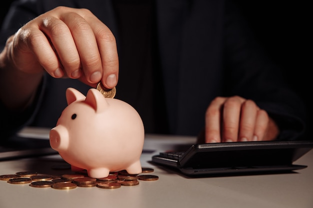 L'uomo d'affari sta contando il profitto su una calcolatrice in ufficio, salvadanaio con monete alla scrivania. economia e gestione del concetto finanziario