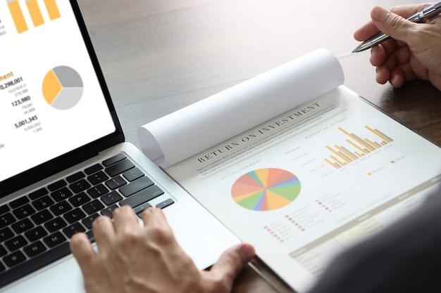 L'uomo d'affari sta esaminando a fondo un rapporto finanziario per un ritorno sull'investimento o un'analisi del rischio di investimento.
