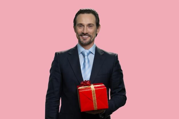 L'uomo d'affari sta tenendo una confezione regalo. isolato su sfondo rosa.