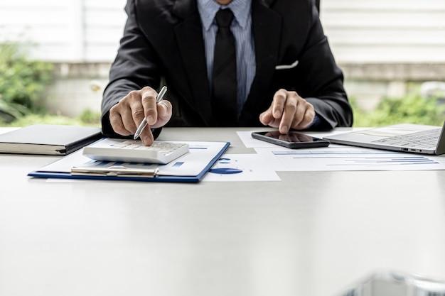Un uomo d'affari sta premendo una calcolatrice per controllare i numeri sui documenti, possiede un'azienda, sta controllando i documenti finanziari dell'azienda nel suo ufficio, i rendiconti finanziari. concetto di gestione finanziaria.