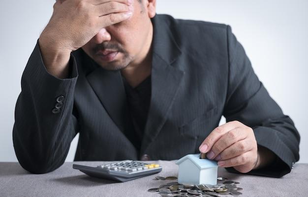 L'uomo d'affari sta mettendo le monete nel salvadanaio di una piccola casa e si sente stressato quando sa che non ha abbastanza soldi per pagare le rate della casa