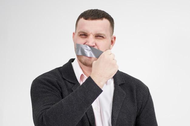 Uomo d'affari sta rimuovendo un pezzo di nastro adesivo che si è coperto la bocca