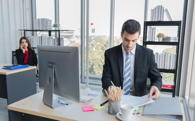 Un uomo d'affari è seduto e controlla la carta sul tavolo che ha computer e documenti