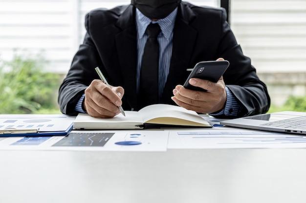 L'uomo d'affari sta prendendo appunti dal proprio cellulare in un taccuino, è il proprietario dell'azienda, sta controllando i documenti finanziari dell'azienda nel suo ufficio. concetto di gestione finanziaria.