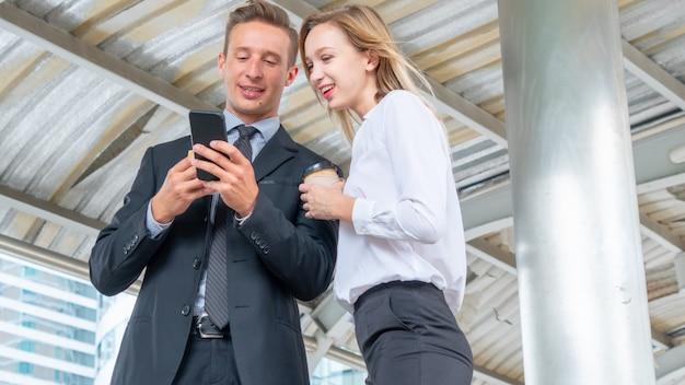 L'uomo d'affari sta parlando e guardando sul telefono cellulare mobile con la donna di affari con gli alimenti a rapida preparazione e la tazza di caffè dell'hamburger della prima colazione della tenuta della mano