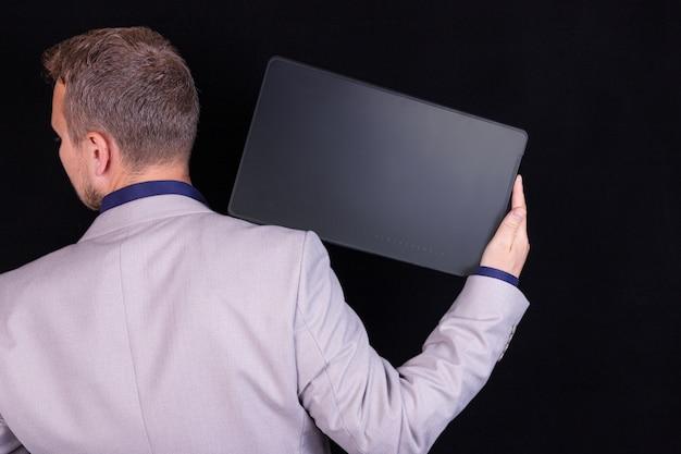 Un uomo d'affari sta lavorando alla sua tavoletta digitale su sfondo nero. concetto di affari, idea.