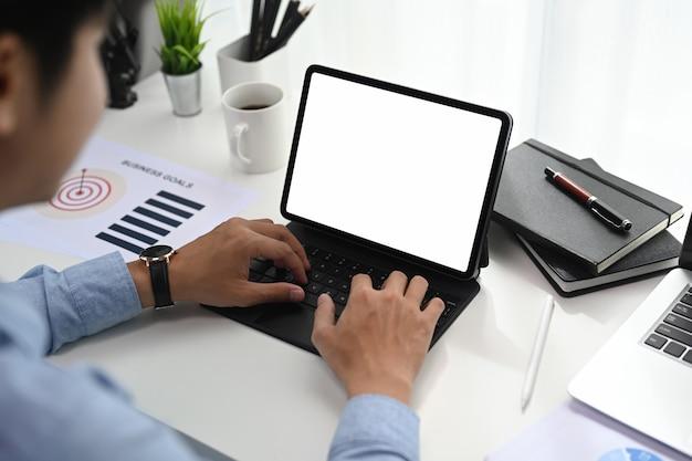 L'uomo d'affari sta lavorando su tablet e sta controllando report finanziari e grafici sul posto di lavoro.