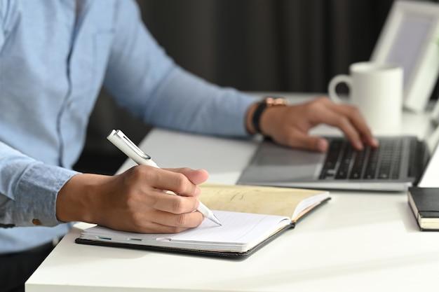 L'uomo d'affari sta lavorando con un nuovo progetto di avvio e sta pianificando un notebook.