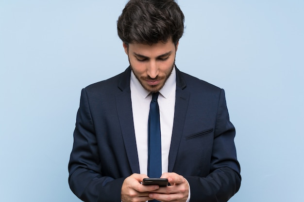 Uomo d'affari sopra isolato muro blu inviando un messaggio con il cellulare