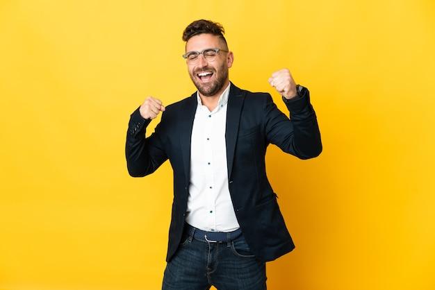 Uomo d'affari sopra la parete gialla isolata che celebra una vittoria