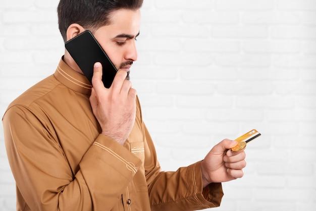 L'uomo d'affari mantiene la carta di credito e parla sul telefono cellulare