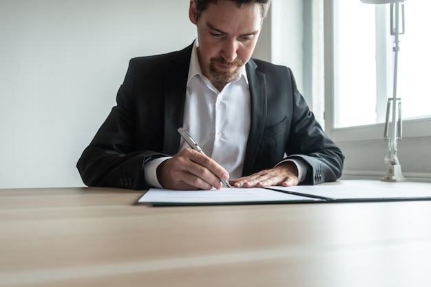 Imprenditore o avvocato seduto alla sua scrivania in ufficio firma un documento o un contratto in un raccoglitore.