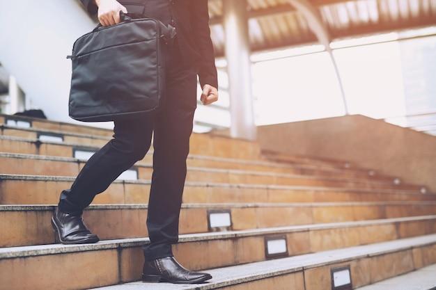 Gambe di uomo d'affari facendo un passo a un livello inferiore su una scala - concetto di decisione di investimento aziendale cattivo